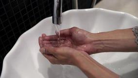 Weibliche Hand öffnet Wasserhahn und VersuchWassertemperatur stock video footage