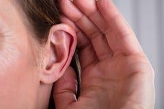 Weibliche Hand auf einem Ohr lizenzfreie stockbilder