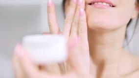 Weibliche Hand der extremen Nahaufnahme, die weiße Feuchtigkeitscreme auf Kinn zutrifft stock video