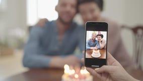 Weibliche Hand des Porträts, die ein Foto auf dem Mobiltelefon der glücklichen lächelnden reifen Frau umarmt mit erwachsenem Enke stock footage
