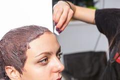 Weibliche Hand des Stilisten abwischend weg von den Überresten der Farbe mit einer Co Stockfotografie