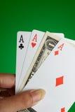 Weibliche Hand, die 3 Asse und eine Dollaranmerkung anhält Lizenzfreie Stockbilder