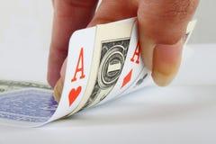 Weibliche Hand, die 3 Asse und eine Dollaranmerkung anhält Stockbilder