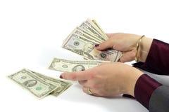 Weibliche Hand, die amerikanische Dollarscheine auf weißem Hintergrund zählt Stockfoto