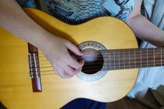 Weibliche Hand, die auf Akustikgitarre spielt Nahaufnahme stockfotos