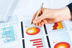 Weibliche Hand, die auf die Finanzwachstumstabelle zeigt Lizenzfreies Stockbild