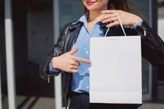 Weibliche Hand, die auf eine leere und weiße Einkaufstasche zeigt Stockbilder