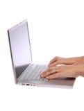 Weibliche Hand, die auf Laptop schreibt Stockbilder