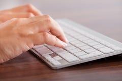 Weibliche Hand, die auf Tastatur schreibt Stockfotografie