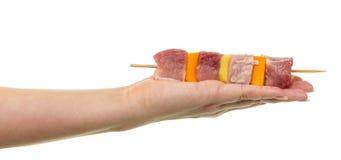 Weibliche Hand, die Aufsteckspindel mit Scheiben rohes Fleisch und Gemüse hält lizenzfreie stockfotografie