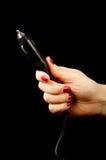 Weibliche Hand, die Autofeuerzeugstecker lokalisiert hält Stockfotos