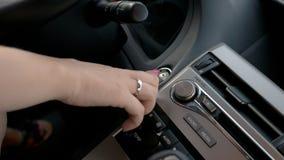 Weibliche Hand, die Automotor, Geschäftsfrau oben fährt Luxusfahrzeug, Abschluss anläßt stockfotografie