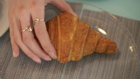 Weibliche Hand, die bei Tisch Hörnchen von der Glasplatte im Caféabschluß oben nimmt lizenzfreies stockfoto