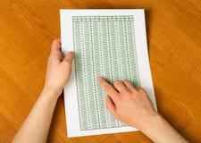 Weibliche Hand, die Blatt mit Berechnungen auf Hintergrundholztisch hält Stockfotografie