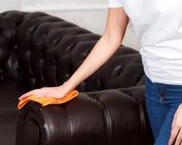 Weibliche Hand, die braune lederne Chester-Couch oder -sofa abwischt Lizenzfreies Stockfoto