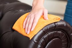 Weibliche Hand, die braunes ledernes Chester-Sofa abwischt Lizenzfreie Stockfotos