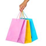 Weibliche Hand, die bunte Einkaufstaschen lokalisiert hält Lizenzfreies Stockfoto