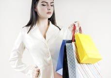Weibliche Hand, die bunten Einkaufstaschekunden stilvoll hält Lizenzfreie Stockfotografie