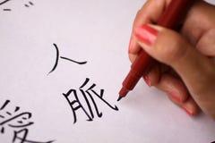 Weibliche Hand, die chinesische Schriftzeichen schreibt lizenzfreies stockfoto