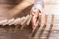 Weibliche Hand, die den Domino vom Fallen stoppt Lizenzfreie Stockbilder
