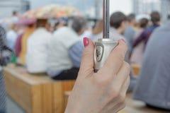 Weibliche Hand, die den Schirmgriff auf einem unscharfen Hintergrund von den Leuten sitzen mit Regenschirmen hält lizenzfreie stockfotos