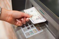 Weibliche Hand, die Dollar entnimmt Lizenzfreie Stockfotos