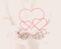 Weibliche Hand, die drei Herzen auf rosa Hintergrund gibt Lizenzfreie Stockbilder