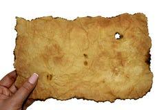 Weibliche Hand, die ein Blatt des alten gelb gefärbten zerknitterten Pergaments hält stockbild