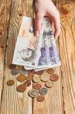 Weibliche Hand, die ein britisches Geld hält Stockfotografie