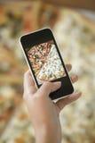 Weibliche Hand, die ein Foto der Pizza macht Stockfoto
