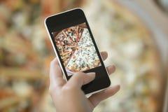 Weibliche Hand, die ein Foto von der Pizza macht Lizenzfreie Stockfotos