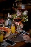 Weibliche Hand, die ein Glas Rotwein an einem Restaurant hält lizenzfreies stockbild
