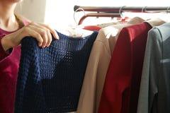 weibliche Hand, die ein Kleid hält Lizenzfreie Stockfotos