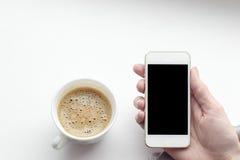 Weibliche Hand, die ein weißes Telefon mit einer schwarzen Anzeige hält Stockbilder