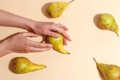 Weibliche Hand, die eine grüne Birne hält stockbilder