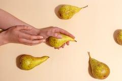 Weibliche Hand, die eine grüne Birne hält stockfoto
