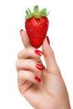 Weibliche Hand, die eine köstliche reife Erdbeere lokalisiert auf Weiß hält Stockbilder