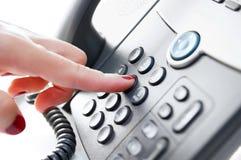 Weibliche Hand, die eine Telefonnummer wählt Lizenzfreie Stockbilder