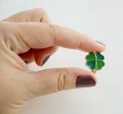 Weibliche Hand, die einen Blattkleecharme hält Lizenzfreies Stockfoto