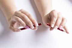 Weibliche Hand, die einen defekten roten Bleistift hält Stockbild