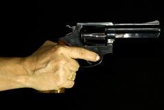 Weibliche Hand, die einen Revolver anhält Stockbild