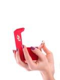 Weibliche Hand, die einen roten Kasten mit Goldring anhält Lizenzfreie Stockbilder