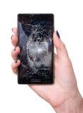Weibliche Hand, die einen Smartphone mit gebrochenem Schirm hält stockbild