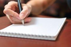 Weibliche Hand, die einen Stift hält und in ein Notizbuch schreibt lizenzfreies stockfoto