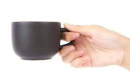 Weibliche Hand, die einen Tasse Kaffee anhält. Stockfotos