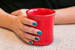 Weibliche Hand, die einen warmen roten Tasse Kaffee hält Stockbild