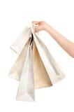 Weibliche Hand, die Einkaufstaschen hält. Lizenzfreie Stockbilder