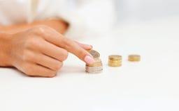 Weibliche Hand, die Euromünzen in Spalten setzt Lizenzfreie Stockbilder