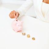 Weibliche Hand, die Euromünzen in Sparschwein setzt Lizenzfreies Stockbild