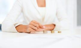 Weibliche Hand, die Euromünzen in Spalten setzt Stockbilder